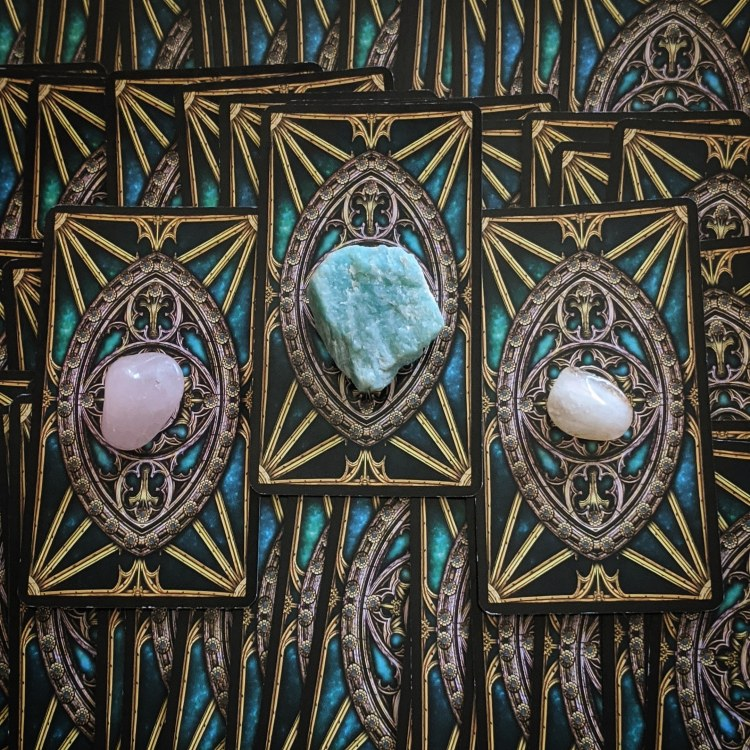 photo of many face down tarot cards with a few crystals placed on top